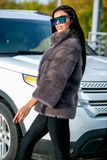 La morenita atractiva hermosa en gafas de sol y un abrigo de pieles se va abajo de la calle en día soleado y miradas Último otoño fotos de archivo