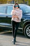 La morenita atractiva hermosa en gafas de sol y un abrigo de pieles se va abajo de la calle en día soleado y miradas Último otoño foto de archivo