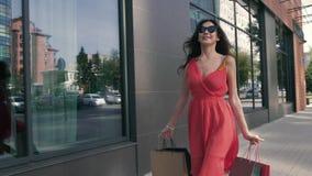La morenita atractiva va por las ventanas de la tienda almacen de metraje de vídeo