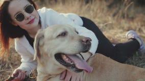 La morenita bonita camina con un Labrador De oro-coloreado en el bosque de la primavera almacen de metraje de vídeo