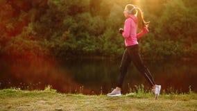 La morenita con el pelo largo en auriculares corre a lo largo del río en el parque por la mañana en la salida del sol en el veran metrajes