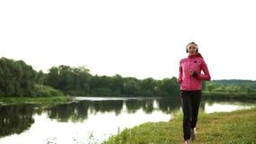 La morenita con el pelo largo en auriculares corre a lo largo del río en el parque por la mañana en la salida del sol en el veran almacen de video