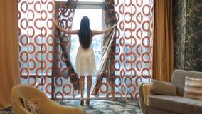 La morenita con el pelo largo en un vestido blanco y talones va a la ventana panorámica y abre las cortinas almacen de video