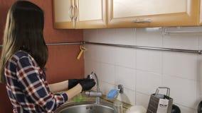 La morenita con el pelo largo en una camisa de tela escocesa saca los guantes de goma almacen de metraje de vídeo