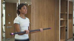 La morenita confiada hermosa está mejorando resistencia por el entrenamiento sano con la barra almacen de video