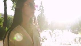 La morenita de la elegancia en gafas de sol elegantes disfruta de rayos soleados de la mañana almacen de video