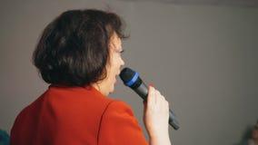 La morenita de la mujer de la Edad Media en traje rojo está hablando en micrófono en conferencia metrajes