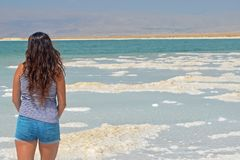 La morenita de pelo largo camina las islas de la sal en el mar muerto, Israel imagenes de archivo
