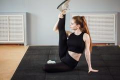 La morenita delgada hermosa que hace cierto estirar ejercita en un gimnasio fotos de archivo