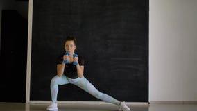 La morenita deportiva presenta para la cámara con pesas de gimnasia azules en sus manos almacen de video