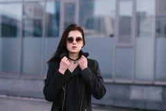 La morenita elegante de la muchacha del retrato al aire libre se vistió en negro y gafas de sol que llevaban en un fondo del fond Imagen de archivo libre de regalías