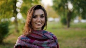 La morenita en la bufanda elegante que sonríe y que mira con confianza la cámara al aire libre almacen de metraje de vídeo