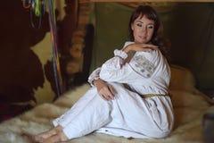La morenita en la camisa pasada de moda de lino blanca con bordado se sienta en una cama medieval imagen de archivo