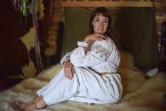 La morenita en la camisa pasada de moda de lino blanca con bordado se sienta en una cama medieval fotos de archivo