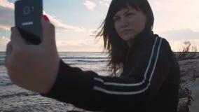 La morenita en la playa hace el selfie en el teléfono almacen de metraje de vídeo