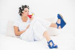 La morenita en rodillos y cuña del pelo calza la consumición de un cóctel Foto de archivo libre de regalías
