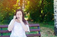 La morenita europea hermosa joven de la muchacha habla en el teléfono en un parque de la ciudad y cubre su cara con sus manos Muj imagen de archivo