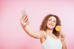 La morenita hermosa con el pelo rizado toma la piruleta del selfie Imagen de archivo