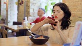 La morenita hermosa hace la foto de plato coreano en su teléfono metrajes