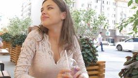 La morenita hermosa joven bebe un cóctel del verano mientras que se sienta en una tabla en un café de la calle Ella es feliz almacen de metraje de vídeo
