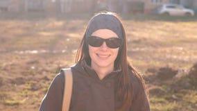 La morenita hermosa joven en gafas de sol mira la cámara y sonríe sentándose en el parque metrajes