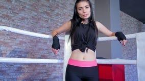 La morenita hermosa se acerca lentamente a la esquina blanca en el ring de boxeo