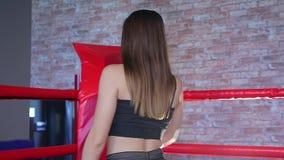 La morenita hermosa se acerca lentamente a la esquina roja en el ring de boxeo almacen de metraje de vídeo