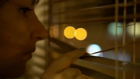 La morenita joven con ojeadas marrones de los ojos a través de la ventana con su finger, empujando abre las persianas imagen de archivo libre de regalías