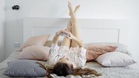 La morenita joven despreocupada está poniendo en cama, las piernas de levantamiento en el cabecero y los mensajes que mecanografí almacen de metraje de vídeo