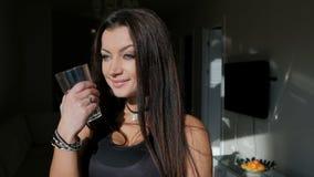 La morenita joven en camiseta negra es agua potable que se coloca en la cocina interior almacen de metraje de vídeo