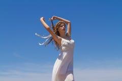 La morenita joven en el vestido débil blanco goza de Foto de archivo libre de regalías