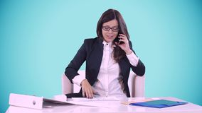 La morenita joven en un fondo azul se sienta detrás de un escritorio en oficina y de hablar en el teléfono En la tabla son los do almacen de metraje de vídeo