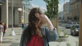 La morenita joven está caminando a lo largo de la calle de la ciudad el tarde del verano almacen de metraje de vídeo