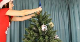 La morenita joven fija la extremidad de cristal encima del árbol de navidad almacen de metraje de vídeo