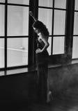La morenita joven hermosa en elegante negro abre el vestido en una suposición Foto de archivo