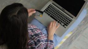 La morenita joven paga compras con la tarjeta de banco en la tienda en línea almacen de metraje de vídeo