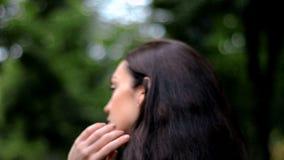 La morenita joven que camina abajo de la calle y mejora el primer del pelo de la mano almacen de metraje de vídeo