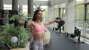 La morenita joven que hace lateral de las pesas de gimnasia aumenta en gimnasio almacen de video