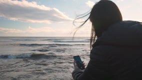 La morenita joven se sienta en la playa rocosa y hace selfies en el teléfono metrajes