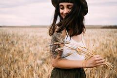 La morenita linda escoge las flores en el campo del trigo Imagen de archivo