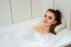 La morenita linda miente en el baño con espuma y mira en la cámara Foto de archivo libre de regalías