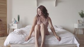La morenita madura hermosa estira lentamente sentarse en la cama por la mañana Sun brilla en ella de la ventana grande almacen de video