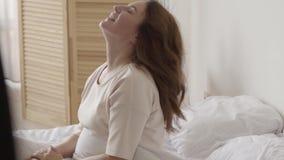 La morenita madura hermosa que despierta lentamente por la mañana en casa, estira y se sienta en la cama Sun brilla en ella de metrajes
