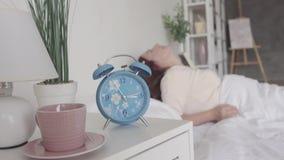 La morenita madura linda que despierta lentamente por la mañana en casa, estira y se sienta en la cama Sun brilla en ella de metrajes