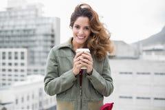 La morenita magnífica sonriente en invierno forma sostener la taza disponible Imagen de archivo