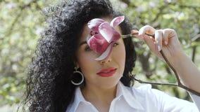 La morenita rizada encantadora goza del olor de la flor de la magnolia metrajes