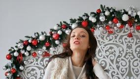 La morenita rizada hermosa sacude su pelo y risas delante de la cámara en el fondo de las decoraciones de la Navidad metrajes
