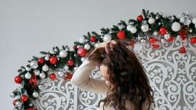 La morenita rizada hermosa sacude su pelo y risas delante de la cámara en el fondo de las decoraciones de la Navidad almacen de video