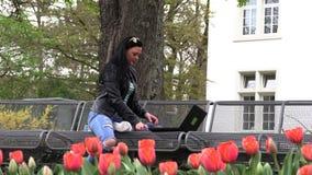La morenita se sienta en un banco de la calle y trabaja en un ordenador almacen de video