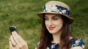 La morenita sensual linda en sombrero del verano está tomando Selfie usando su Smartphone al aire libre almacen de video
